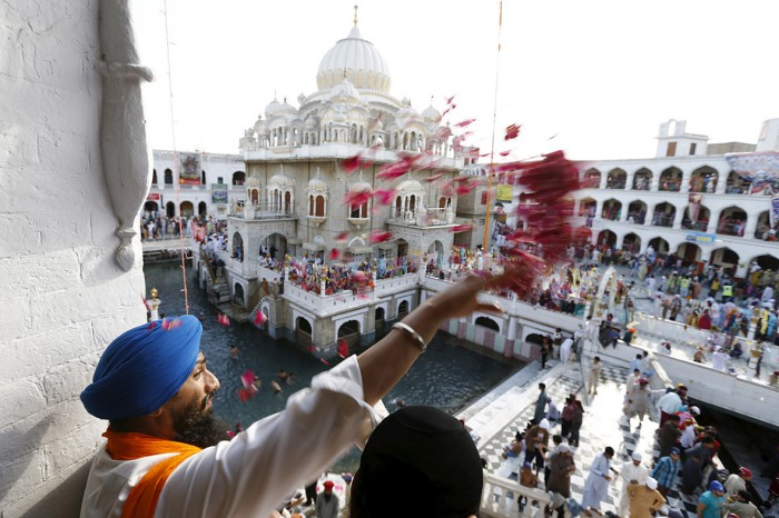 A Sikh devotee throws petals as the procession passes by during the Vaisakhi festival at Panja Sahib shrine in Hassan Abdel(Caren Firouz-Reuters) (98K)